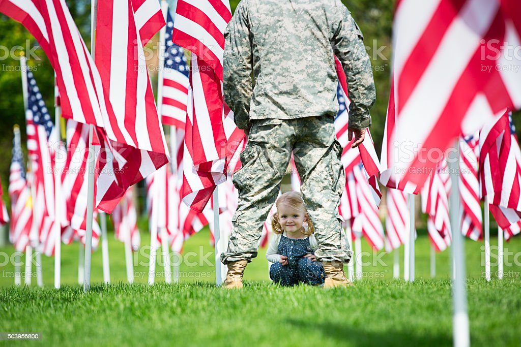 Toddler girl looking through the legs of an American Soldier stock photo