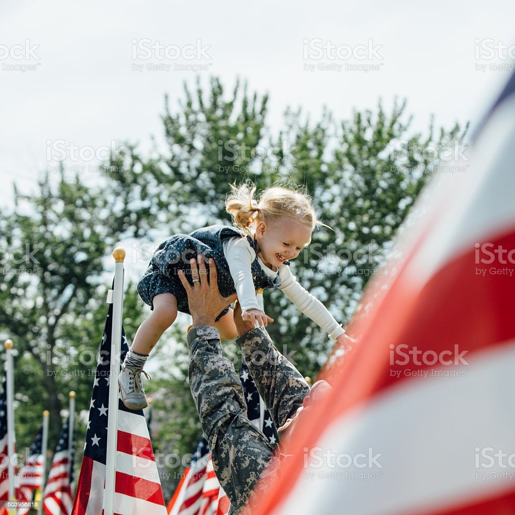 Toddler girl playing happily with an American Soldier in uniform stock photo