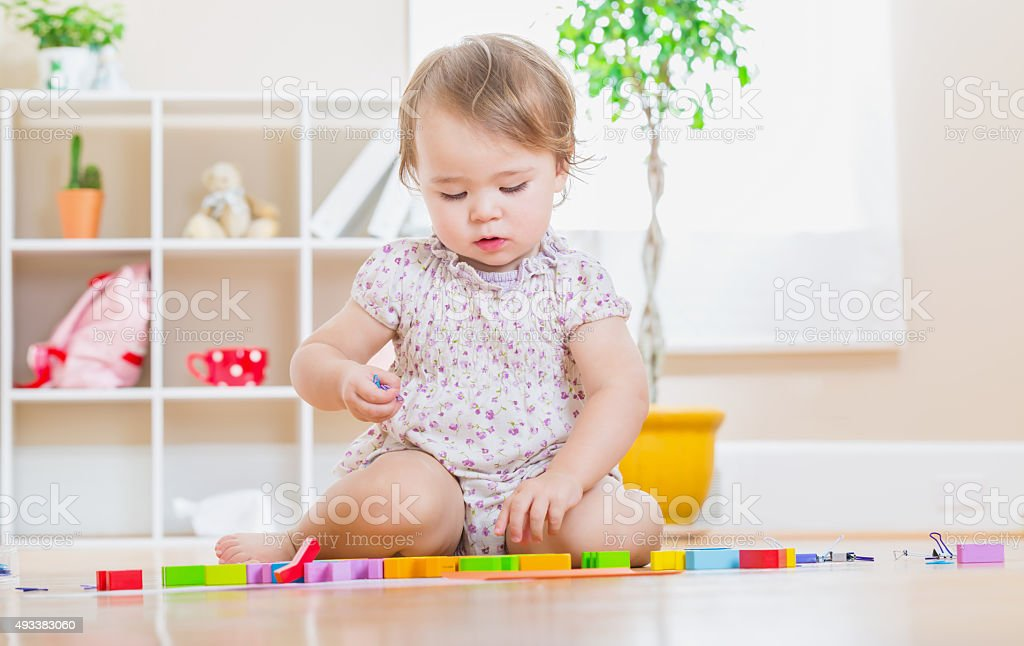 Toddler girl playing her toys stock photo