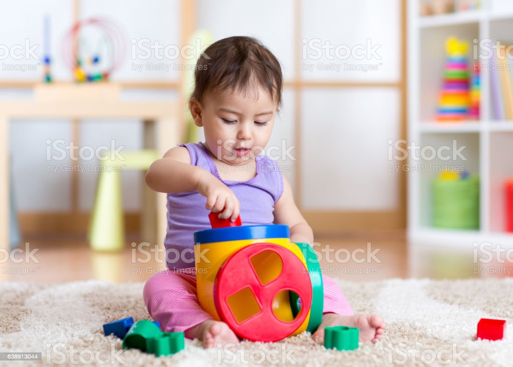 toddler girl playing indoors with sorter toy sitting on soft stock photo