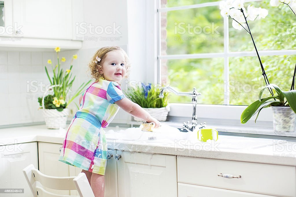 Toddler girl playing with foam into sink in white kitchen stock photo