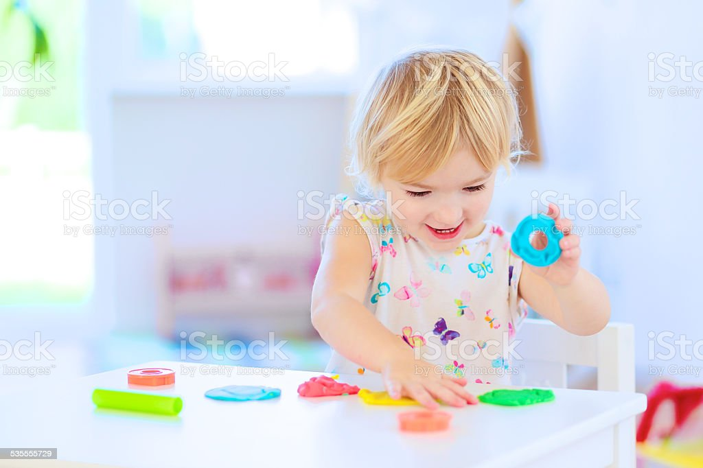 Toddler girl playing with plasticine stock photo