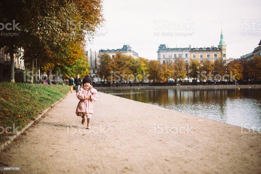 Toddler girl running by the lakes in Copenhagen stock photo