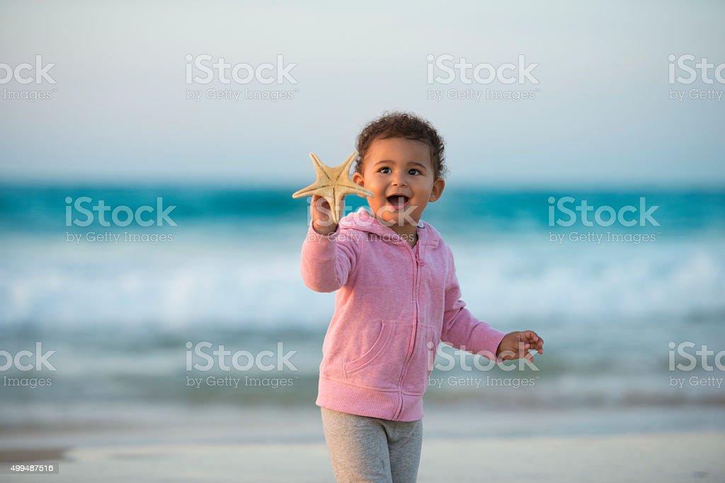 Toddler girl showing starfish. stock photo