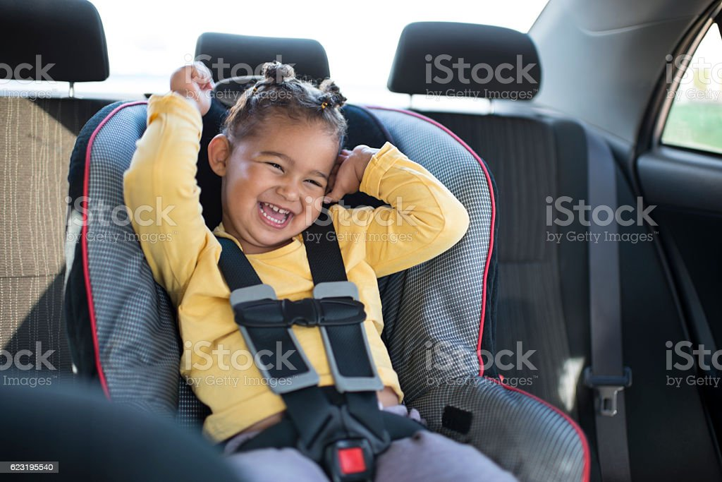 Toddler girl sitting in safety car chair. stock photo