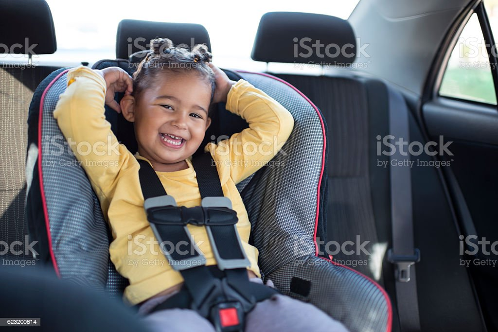 Toddler girl sitting on safety car chair. stock photo