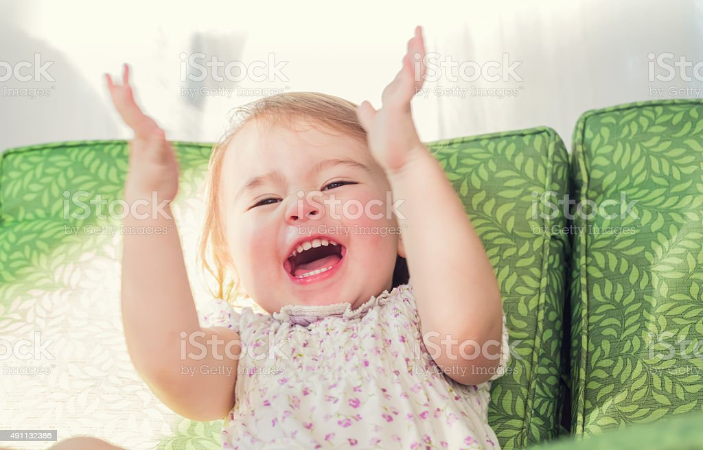 Toddler girl smiling and clapping her hands stock photo
