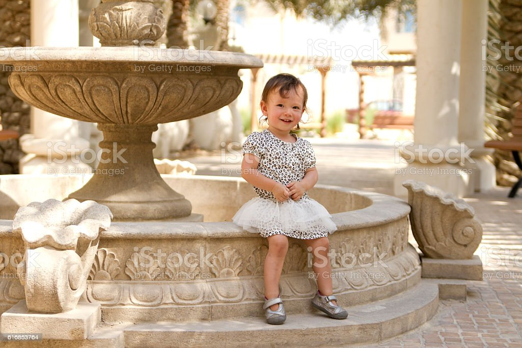 Toddler Girl Smiling and Sitting Outside stock photo