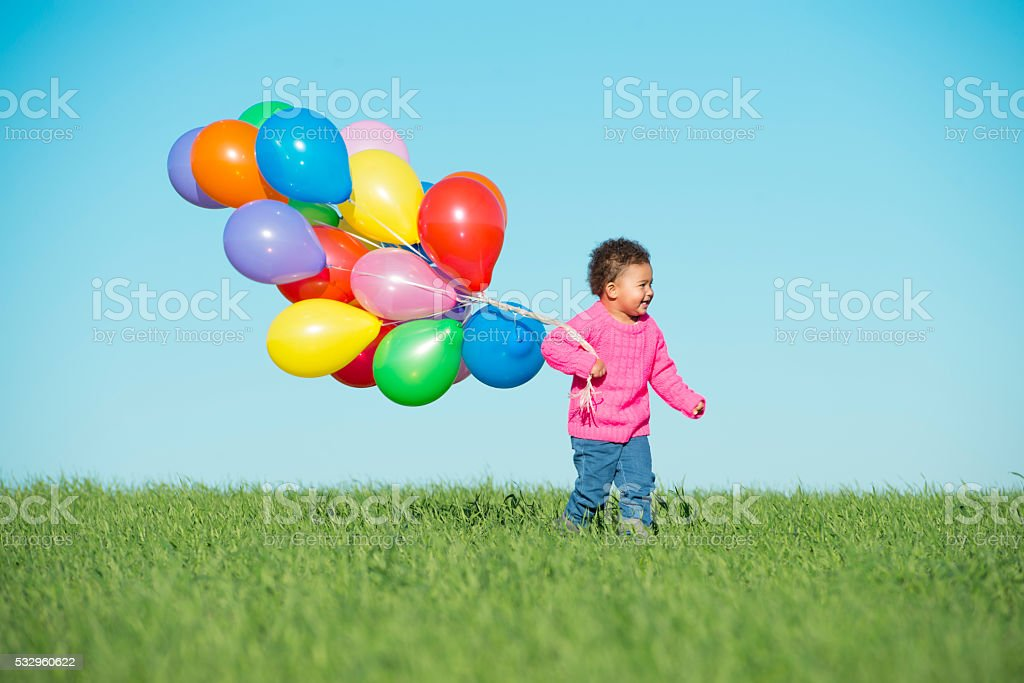Toddler girl walking on spring field. stock photo