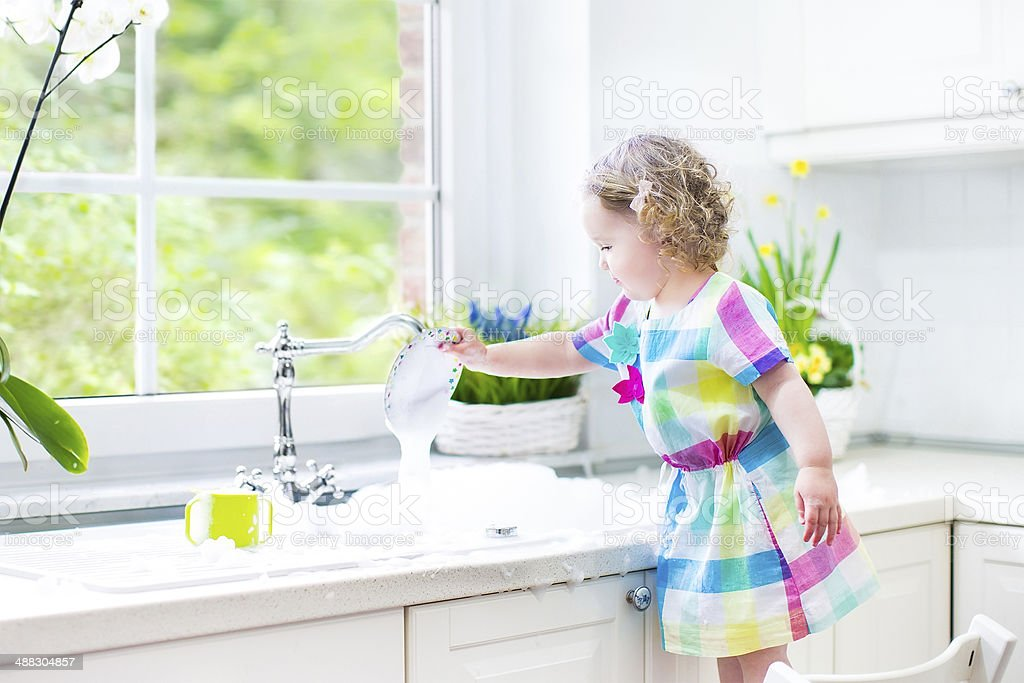 Toddler girl washing dishes in kitchen with garden view window stock photo