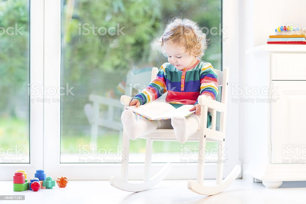 Toddler girl with curly hair wearing colorful dress reading book stock photo