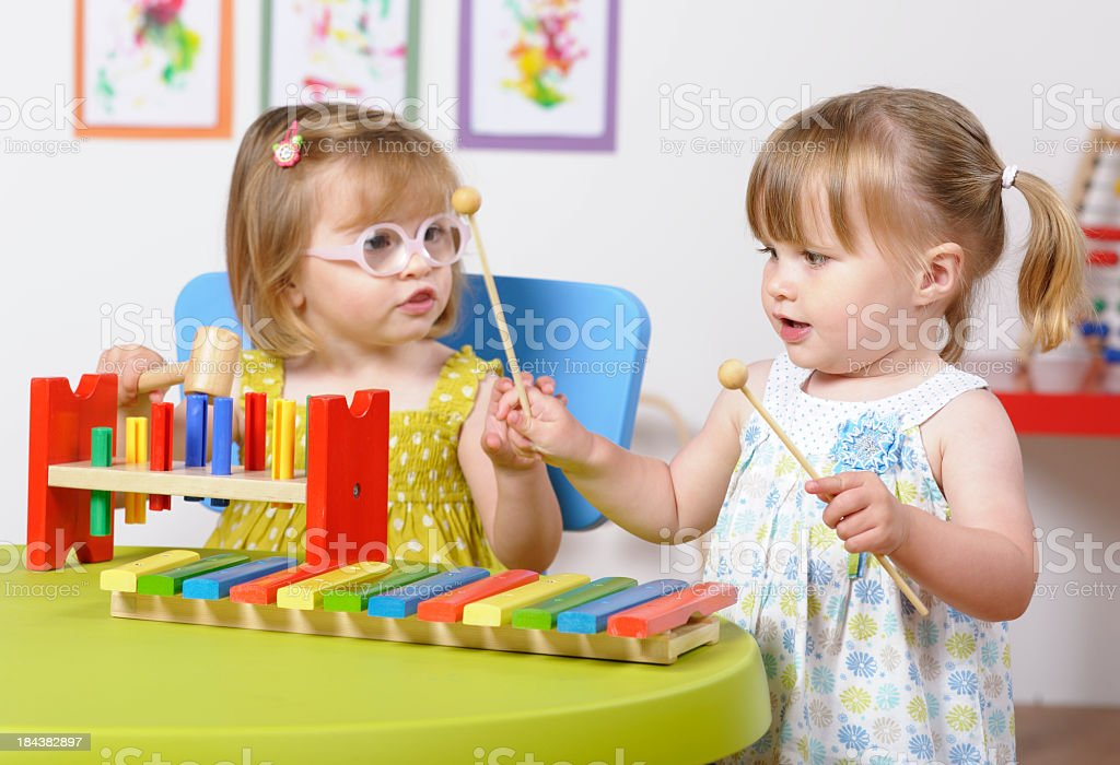 Toddler Girls Interacting  And Enjoying Music In A Nursery Setting stock photo