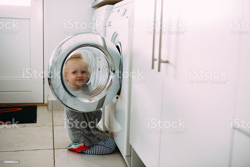 Toddler helping with the laundry stock photo