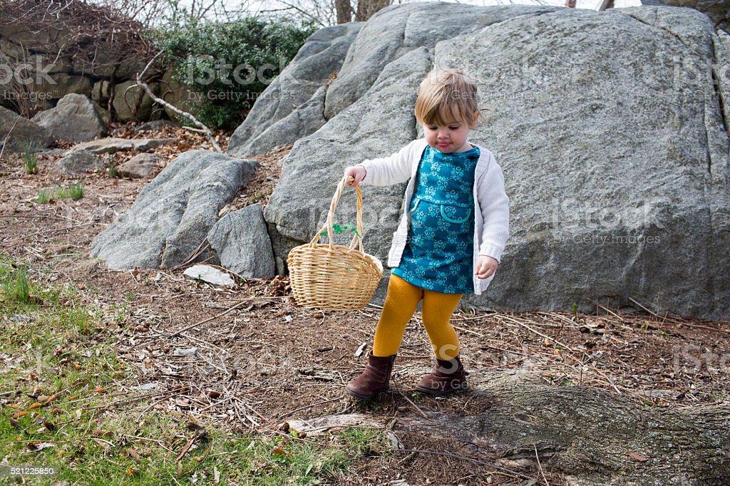 Toddler hunting for Easter eggs on Easter Sunday. stock photo