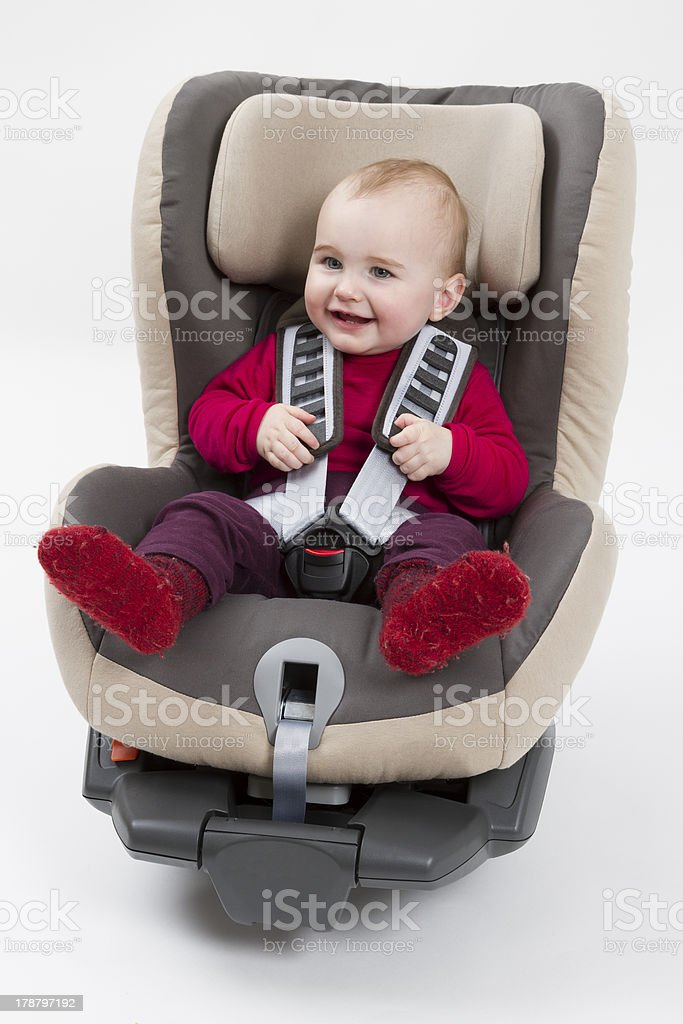toddler in booster seat for a car, light background royalty-free stock photo