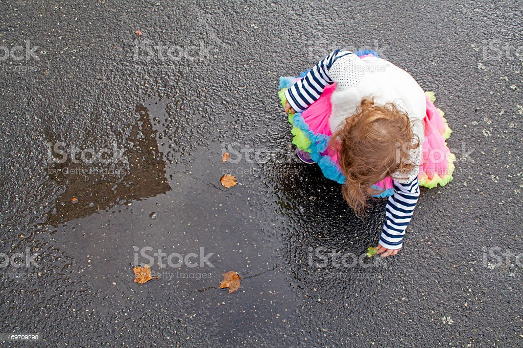 Toddler in Bright Clothes Playing with leaves in Rain Puddle stock photo