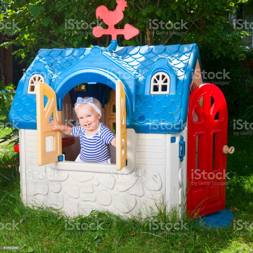 Toddler in kids playhouse outdoor stock photo