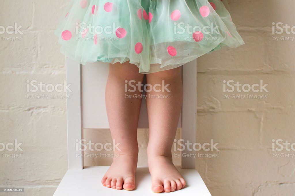 Toddler in polka dot skirt on chair (cropped) stock photo
