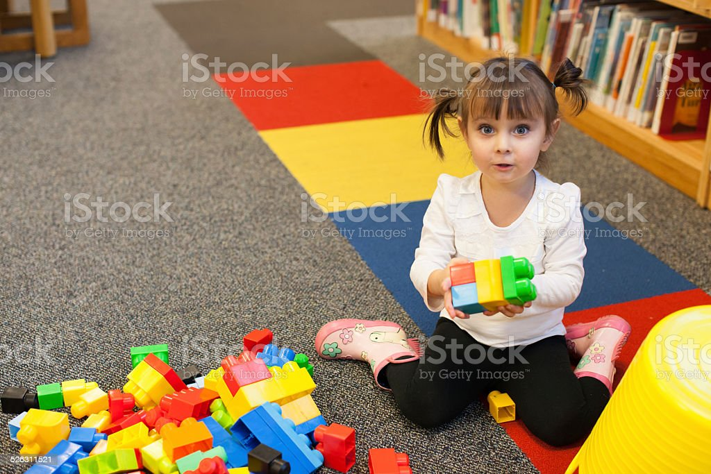 Toddler is Playing With Blocks At the Library stock photo