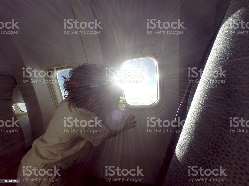 Toddler is watching sun trough window airplane stock photo
