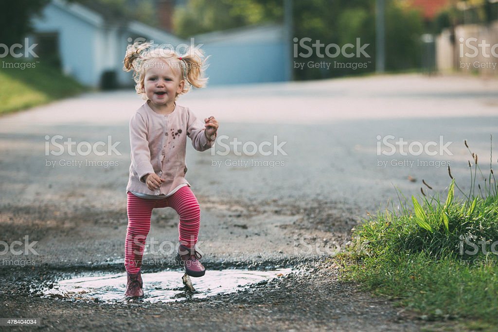 Toddler jumping in a puddle stock photo