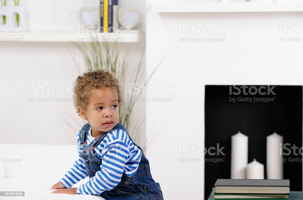 Toddler Leaning On A Sofa And Looking Over His Shoulder stock photo