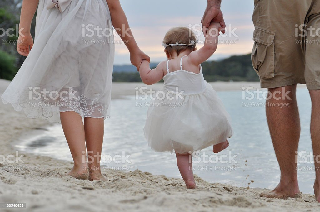 Toddler learning to walk at the beach stock photo