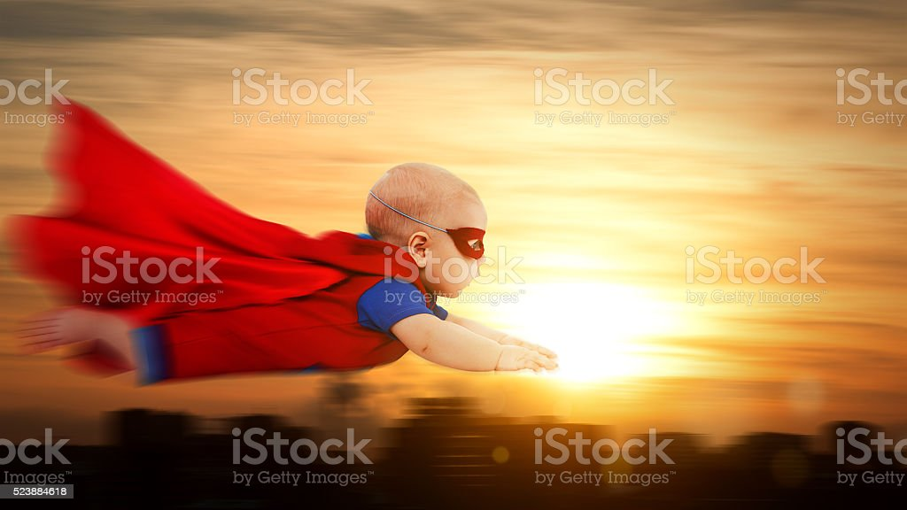 toddler little baby superman superhero with red cape flying thro stock photo