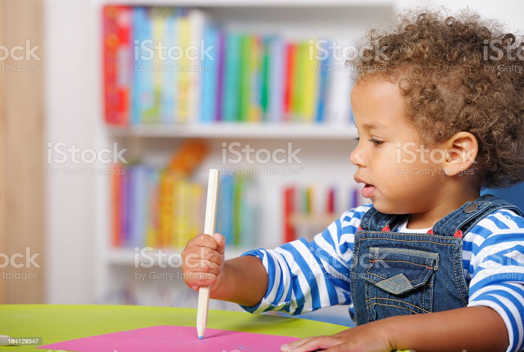 Toddler Looking At A Pencil While Doing Art And Craft stock photo