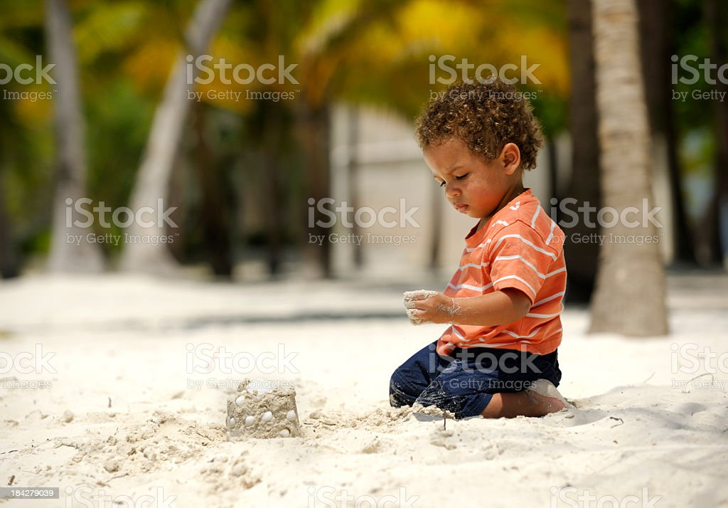 Toddler Looking At Sand Castle On A Sandy Beach stock photo