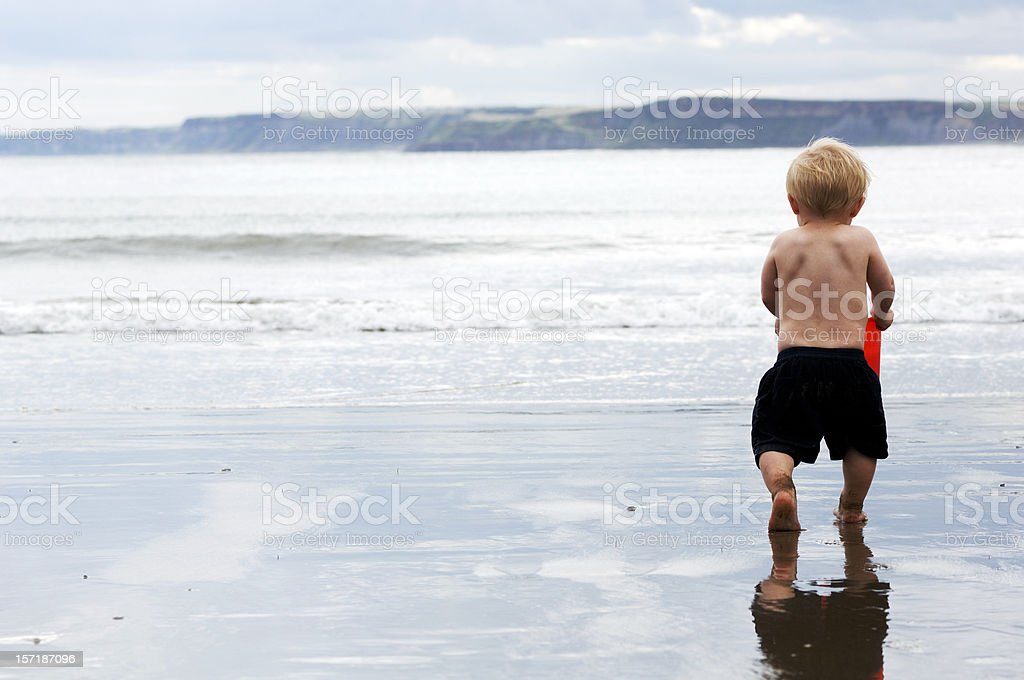 Toddler on beach running to the sea stock photo