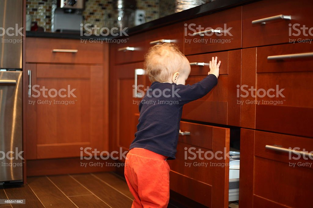 Toddler opening kitchen drawers stock photo