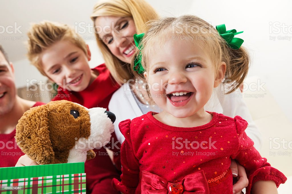 Toddler opening presents with family on Christmas day stock photo