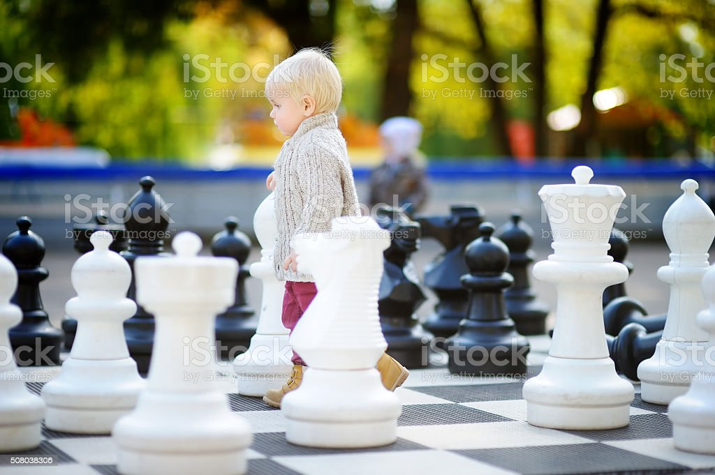 Toddler playing giant chess outdoors stock photo