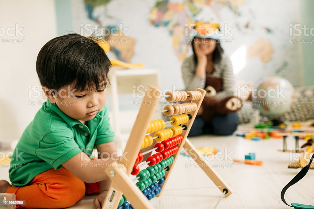 Toddler playing with abacus stock photo