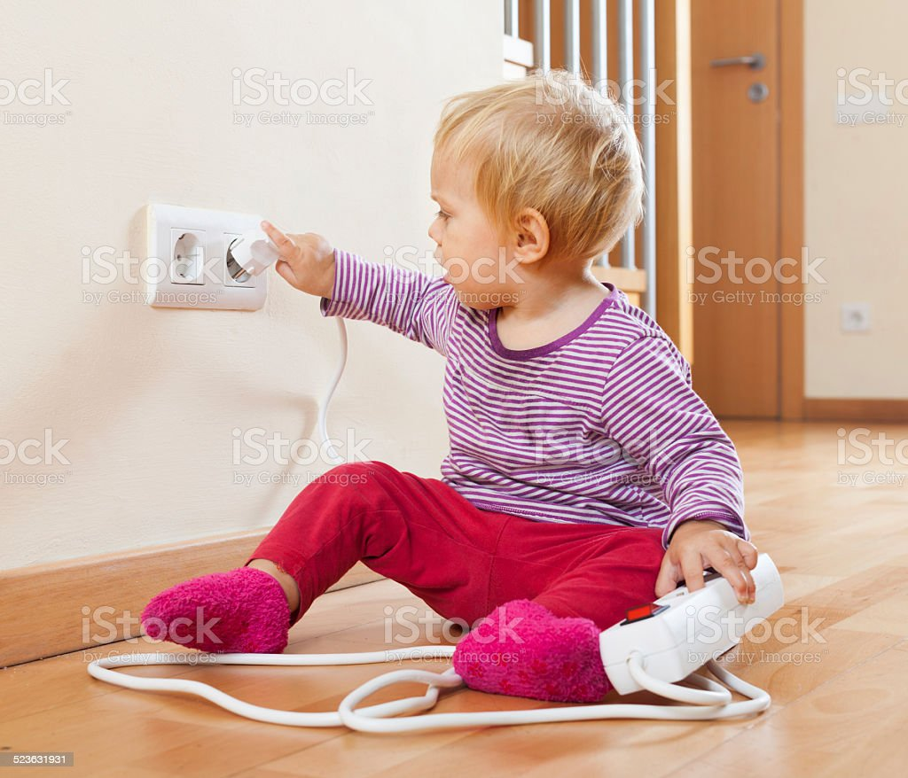 Toddler playing with extension cord and  electric outlet stock photo