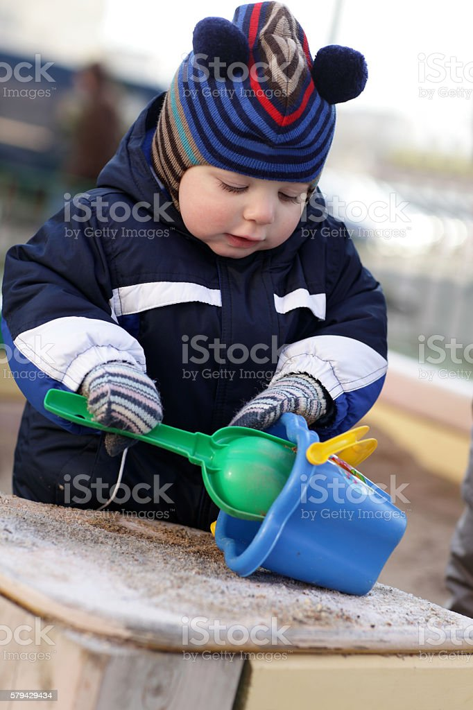 Toddler playing with shovel and bucket stock photo