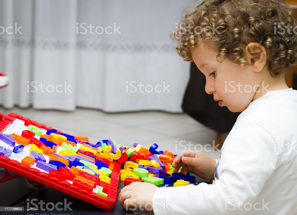 Toddler (2 years old) plays with toy letters stock photo