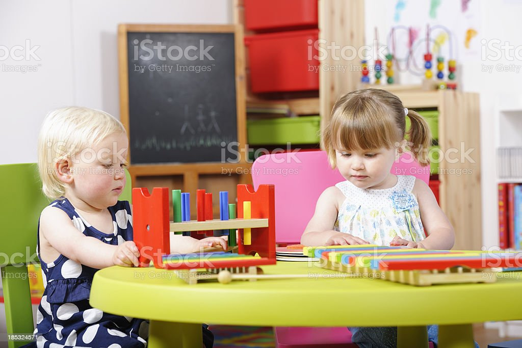 Toddler/ Pre-Schooler And Peer Playing With  Multi-coloured Toy At Nursery royalty-free stock photo
