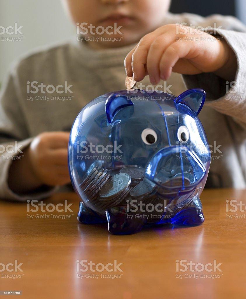 Toddler Putting or Saving Money Into Blue Piggy Bank stock photo