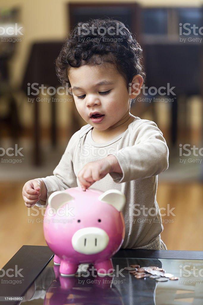 Toddler Saving Money in a Piggy Bank royalty-free stock photo