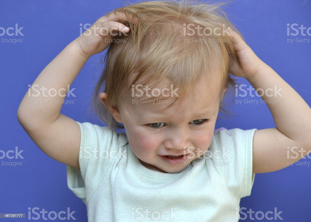 Toddler scratching head stock photo