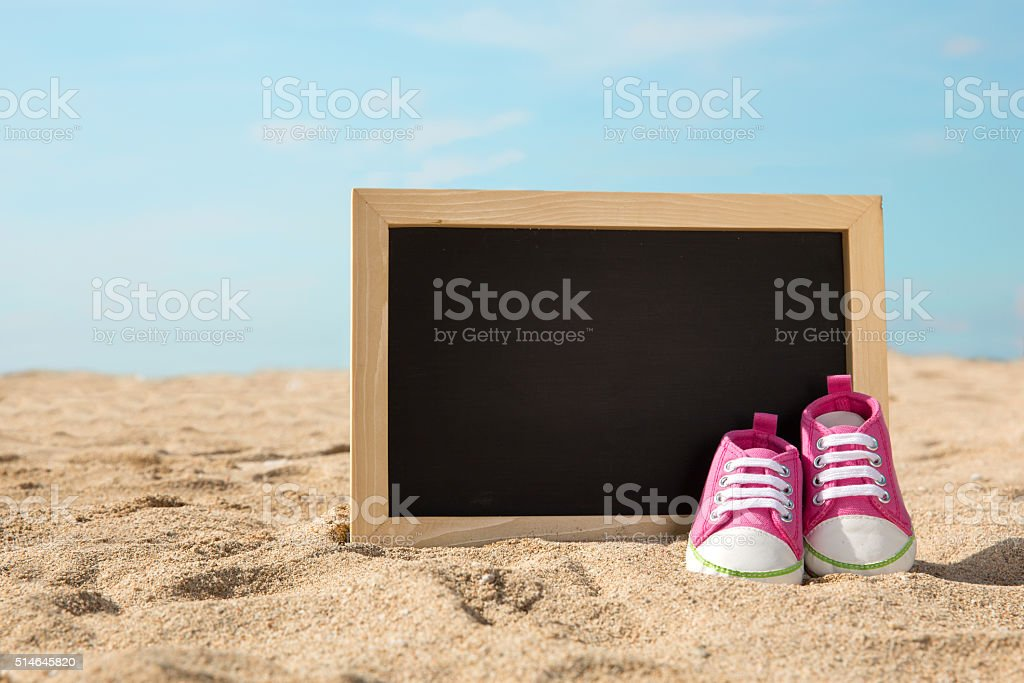 Toddler shoes and mini chalk board on the sand stock photo