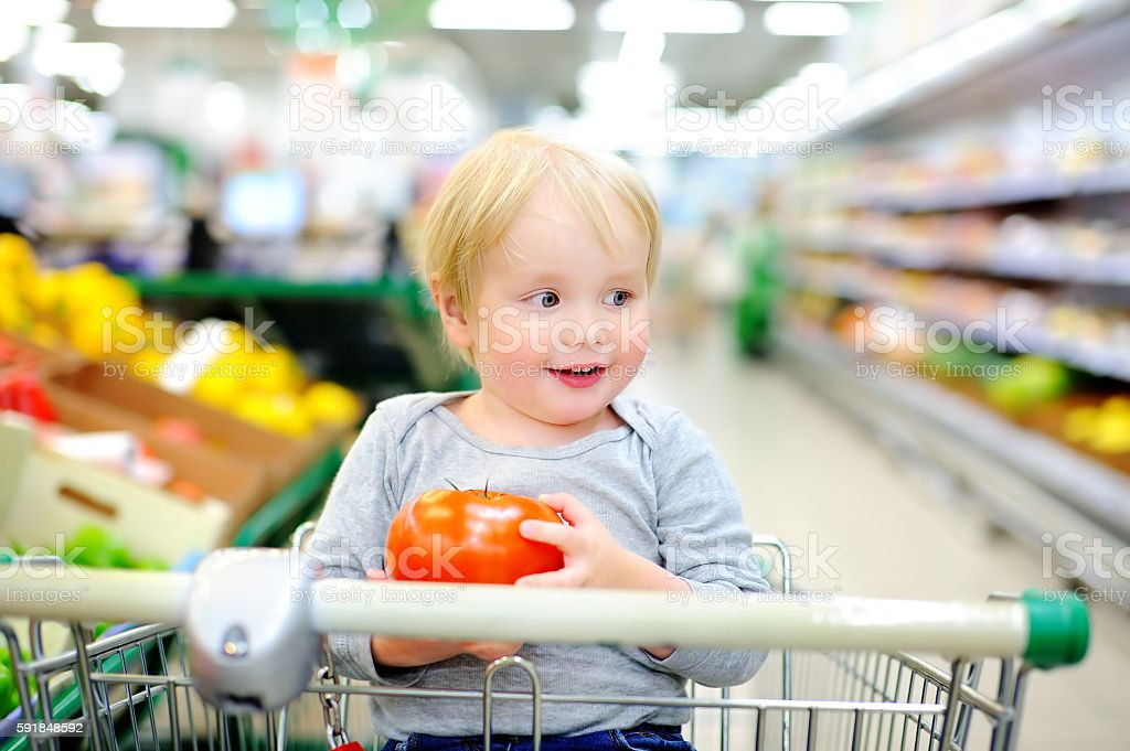 Toddler sitting at the shopping cart in a supermarket stock photo