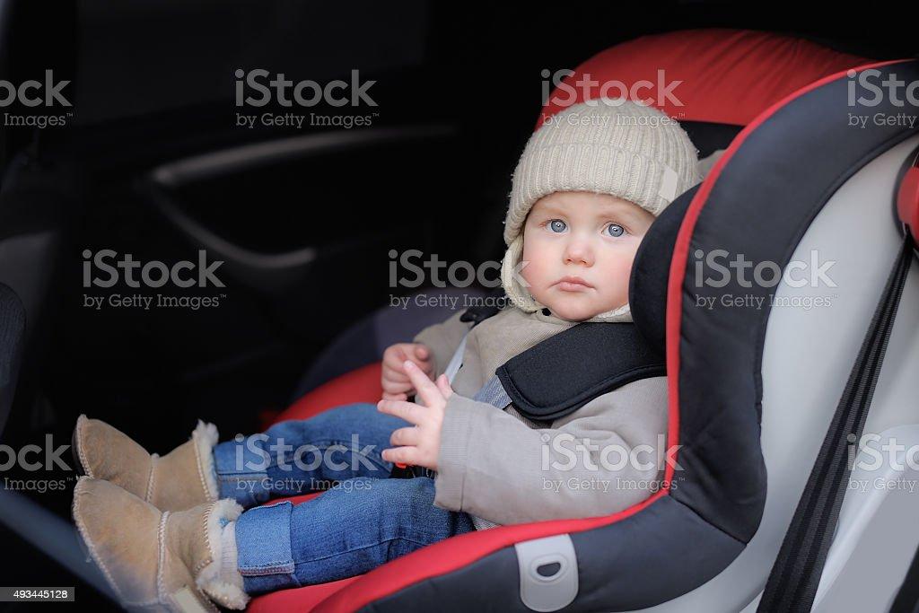 Toddler sitting in car seat stock photo