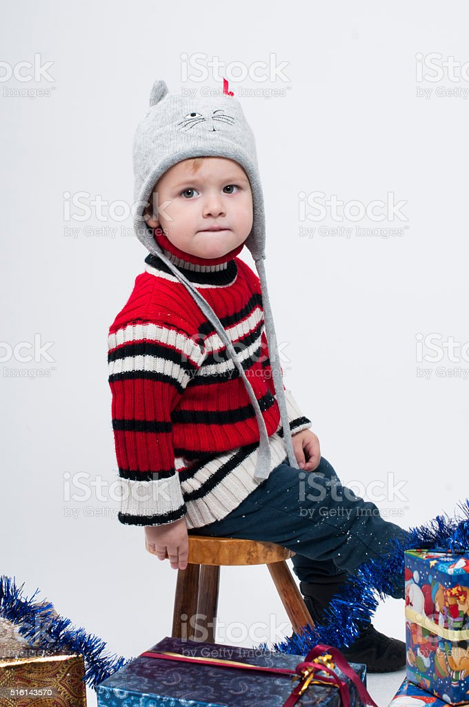 Toddler sitting on a small stool in a cap stock photo