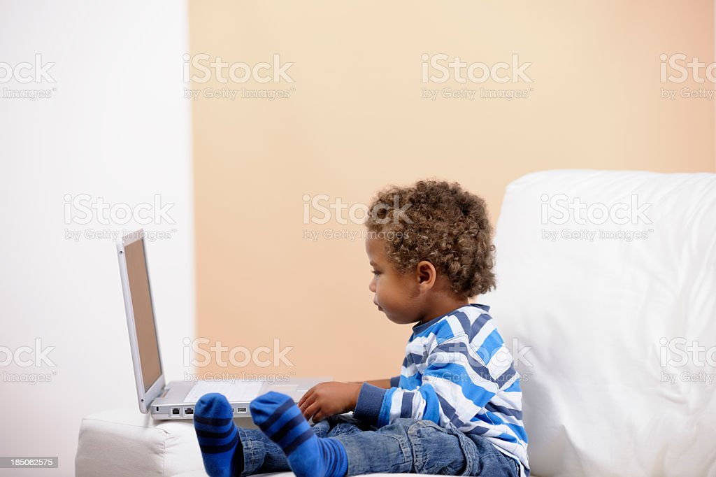 Toddler Sitting On Couch/ Sofa And Using The Computer stock photo