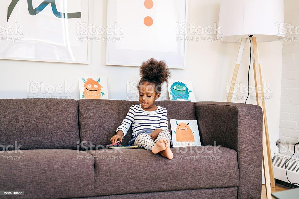 Toddler sitting on sofa stock photo