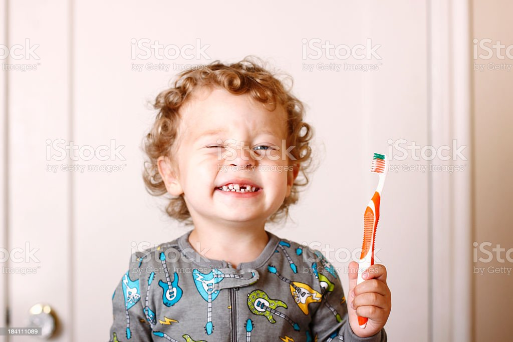 Toddler smiling while holding a toothbrush stock photo