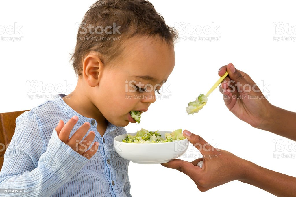 Toddler spitting out his vegetables stock photo